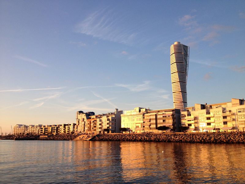 The apartments and Turning Torso sky scraper in Vastra Hamnen Western Harbour at a golden sunset in Malmo Sweden.