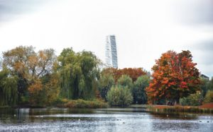 The iconic skyscraper building Turning Torso in the background behind Autumn trees in Pildammsparken in Malmo, Sweden. Filtered image with soft effect.